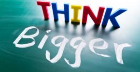 Think bigger concept, words on blackboard